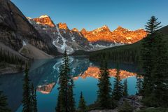 Moraine lake at sunrise in Canadian Rockies,. Beautiful sunrise under turquoise waters of the Moraine lake with snow-covered peaks above it in Banff National royalty free stock photos