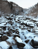 Moraine with a stream in the winter mountains Stock Photography