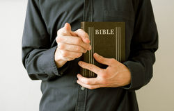 Moralizing, missionary, oppression and guilty. Man, priest or believer, is holding Holy Bible, main religious text of Christianity. Right hand is pointing stock image