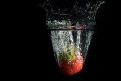 A morango cai profundamente sob a água Fotografia de Stock
