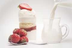 Morango e sobremesa frescas Derrame o leite dentro do vidro fotografia de stock