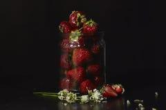 Morango em um frasco de vidro em um fundo escuro Fotos de Stock Royalty Free