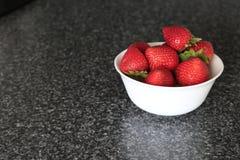Morango fresca apetitosa em uma bacia branca em um fundo cinzento Imagens de Stock