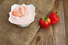 Morango fresca com o iogurte na bacia branca no fundo de madeira Fotos de Stock