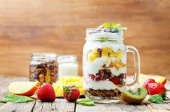 Morango, manga, quivi, mirtilo, alaranjados com iogurte grego e Foto de Stock