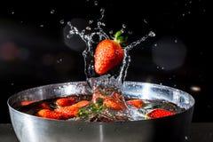 A morango que cai na água com espirra da água Imagens de Stock