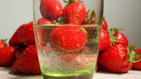 Morango que cai no vidro na água com respingo, conceito saudável do alimento filme