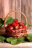 Morangos doces frescas na cesta em uma tabela de madeira Imagem de Stock