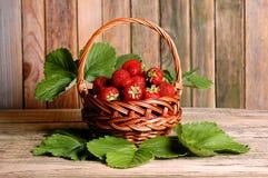 Morangos doces frescas na cesta em uma tabela de madeira Fotos de Stock