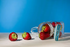 Morangos e um frasco de vidro completamente das morangos que encontram-se para baixo sobre Fotografia de Stock Royalty Free