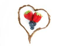 Morangos e uvas-do-monte em um coração do chocolate Foto de Stock