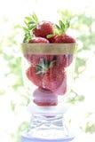 Morangos em um copo de vidro em um fundo colorido Foto de Stock