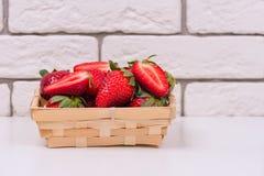 Morangos frescas em uma cesta de madeira em uma tabela branca e contra uma parede de tijolo fotos de stock
