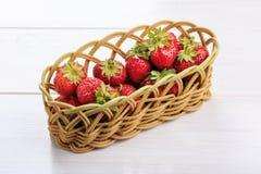 Morangos frescas em uma cesta de vime em uma tabela branca imagem de stock