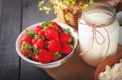 Morangos frescas maduras, leite em um jarro e requeijão caseiro na mesa de cozinha Imagem de Stock Royalty Free
