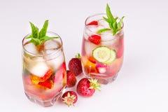 Morangos no volume em um fundo branco, um vidro com uma bebida Fotografia de Stock Royalty Free