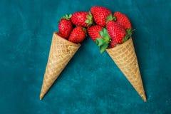 Morangos orgânicas maduras em cones de gelado do waffle, imitação de derramamento, obscuridade - fundo azul Fotografia de Stock Royalty Free