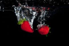Morangos que espirram na água fotografia de stock royalty free