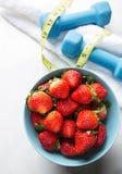 Morangos saudáveis e em uma bacia com pesos e fita métrica Fotografia de Stock
