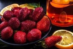 Morangos vermelhas em uma placa preta, em umas fatias do limão e em um chá de vidro com limão Imagens de Stock
