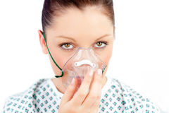 Morbid caucasian woman holding an oxygen mask. Morbid caucasian woman wearing a mask looking at the camera against white background Stock Photography