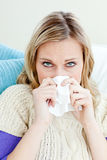 Morbid woman using a tissue sitting on a sofa. At home in the living-room Stock Photo
