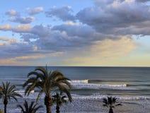 Morbidamente gli insiemi del sole sopra la spiaggia Immagini Stock