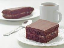 Morceau carré de gâteau de chocolat avec le remplissage crème 'brownie' faits maison de chocolat disposés du plat blanc Foyer sél photos stock