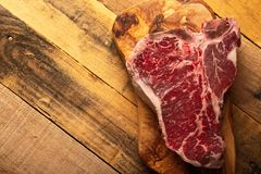 Morceau cru frais de bifteck de boeuf marbré sur une planche à découper, sur un fond en bois Menu de restaurant, menu à la maison images stock