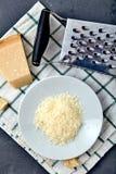 Morceau d'un parmesan et d'un fromage râpé photo stock