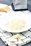 Morceau d'un parmesan et d'un fromage râpé image libre de droits