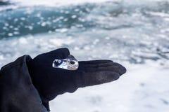 Morceau de belle glace transparente se trouvant sur la main de woman's Photographie stock