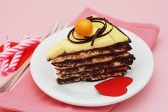 Morceau de chocolat de gâteau avec les coeurs et les bougies de papier, sur le fond rose Dessert de partie ou d'anniversaire dans Images stock