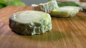 Morceau de fromage de ch?vre naturel Le Sainte Maure tombant sur une surface en bois banque de vidéos