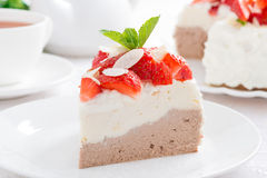morceau de gâteau avec de la crème, les fraises et le thé fouettés Image libre de droits