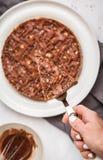 Morceau de gâteau de chocolat cru de vegan avec les écrous et le chocolat dans le whi Image libre de droits