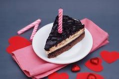 Morceau de gâteau de chocolat pour le jour du ` s de Valentine Gâteau de papier rouge d'Arround de coeurs Fond gris Serviette ros Photo libre de droits