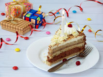 Morceau de gâteau de banane de chocolat décoré des rosettes de crème, des baies et des bougies sur le fond en bois clair Annivers Images libres de droits