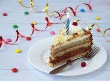 Morceau de gâteau de banane de chocolat décoré des rosettes de crème, des baies et des bougies sur le fond en bois clair Annivers Image stock