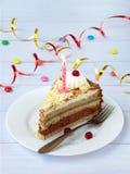 Morceau de gâteau de banane de chocolat décoré des rosettes de crème, des baies et des bougies sur le fond en bois clair Annivers Images stock