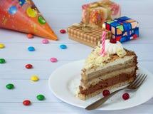 Morceau de gâteau de banane de chocolat décoré des rosettes de crème, des baies et des bougies sur le fond en bois clair Annivers Photos stock