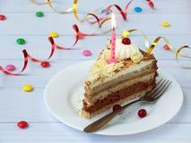 Morceau de gâteau de banane de chocolat décoré des rosettes de crème, des baies et des bougies sur le fond en bois clair Annivers Photographie stock libre de droits