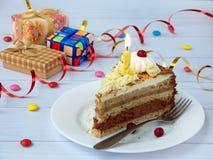 Morceau de gâteau de banane de chocolat décoré des rosettes de crème, des baies et des bougies sur le fond en bois clair Annivers Image libre de droits