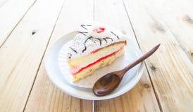 Morceau de gâteau de vanille sur la table en bois Photographie stock libre de droits