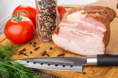 Morceau de la poitrine, bouteille avec le condiment, tomates, épices, aneth, couteau sur la planche à découper sur la table en bo image libre de droits