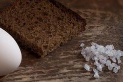 Morceau de pain de seigle brut avec du sel et l'oeuf photos stock
