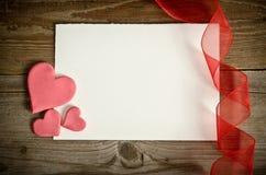 Morceau de papier avec des coeurs et de ruban sur un conseil en bois Image stock