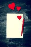 Morceau de papier avec des coeurs et de stylo sur le vieux fond de tableau Image stock