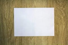Morceau de papier blanc vide sur le fond en bois Photographie stock libre de droits