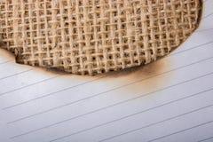 Morceau de papier brûlé sur une toile de toile Photos libres de droits